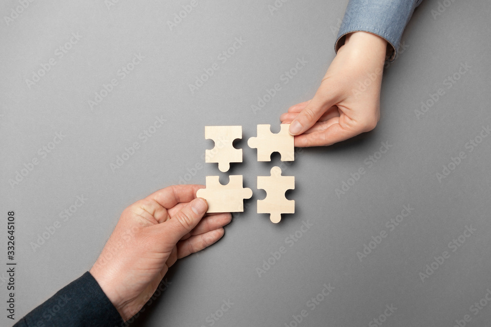 Fototapeta Two hands connect puzzles on a grey background. Cooperation and teamwork in business. Collaboration people for success.