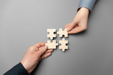 Two Hands Connect Puzzles On A Grey Background. Cooperation And Teamwork In Business. Collaboration People For Success.