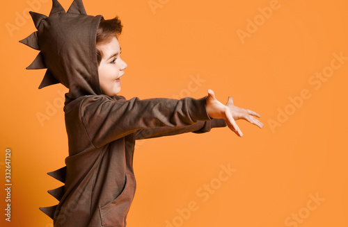Nice smiling kid boy in hoodie with dinosaurus spikes at his back and cowl holds Canvas Print