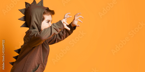 Photo Kid boy in hoodie with dinosaurus spikes at his back and cowl playing t-rex hold