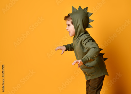 Kid boy in hoodie with dinosaurus spikes at his back and cowl act as a t-rex wit Canvas Print