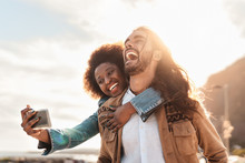 Happy Smiling Couple Taking Selfie With Mobile Smartphone Outdoor - Young Trendy People Having Fun During Vacations - People Technology Addicted And Travel Trend Lifestyle Concept