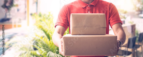 Photo Delivery man by sending box of parcel to customers service at home as having cor