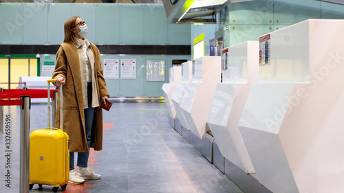 Obraz Woman with luggage stands at almost empty check-in counters at the airport terminal due to coronavirus pandemic/Covid-19 outbreak travel restrictions. Flight cancellation.Quarantine all over the world - fototapety do salonu