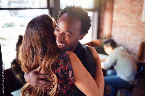 Fotografie, Obraz Couple Greeting Each Other With Hug As They Meet In Coffee Shop