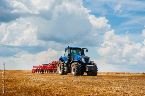 Photo blue tractor in the field, agricultural machinery work, field and beautiful sky