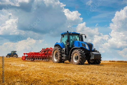 Fotografie, Obraz blue new tractor with red harrow in the field against a cloudy sky, agricultural