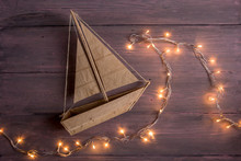 Travel And Adventure Creative Concept - Toy Boat On A Wooden Background. Christmas Lights As A Sea Waves