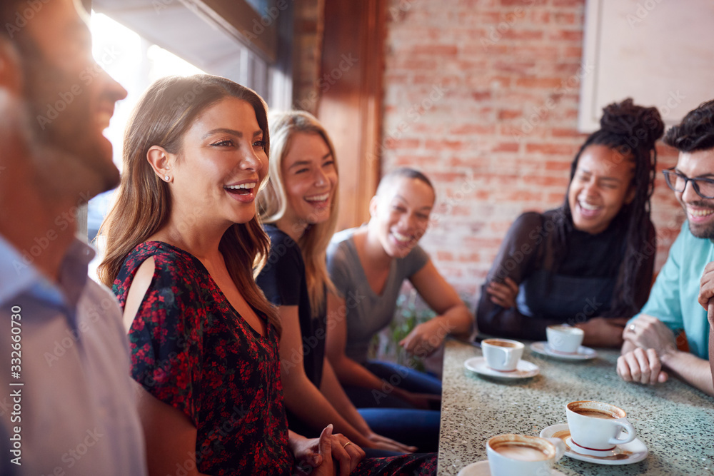 Fototapeta Group Of Male And Female Friends Meeting For Coffee Sitting At Table Together