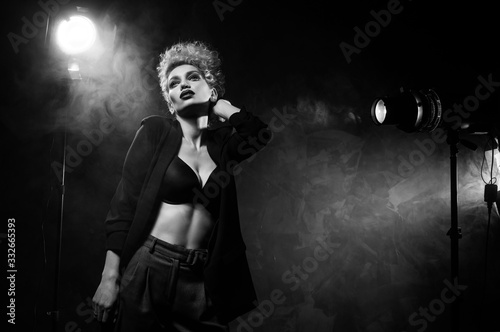 Fotografía A beautiful blonde girl with an elegant hairstyle and large breasts, wearing a bra, trousers and a blazer, artistically poses in the rays of spotlights in the smoke