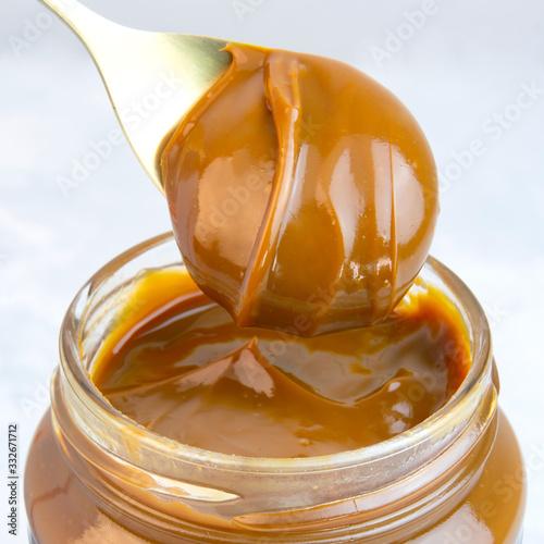Fotografia Closeup of scoop and jar full of dulce de leche or milk caramel spread