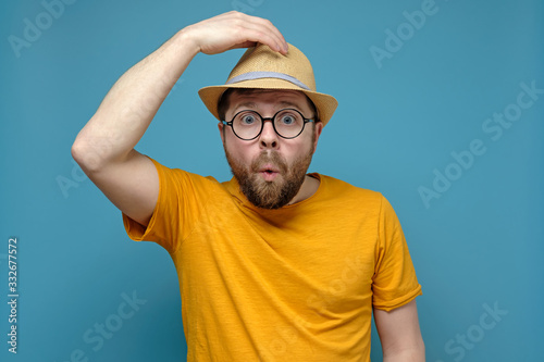Surprised Caucasian man in round glasses clings to his hat, as if greeting someone, on a blue background Canvas Print