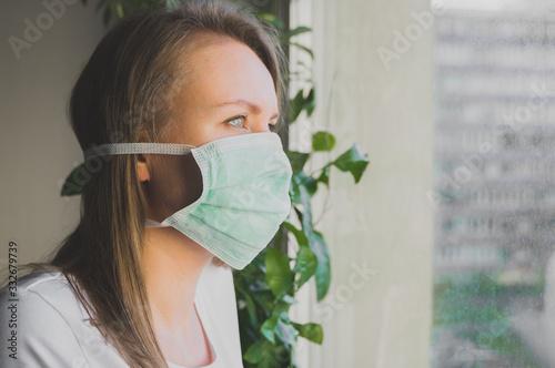 Woman in medical mask near window. Quarantine at home. Canvas Print