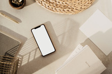 Flatlay Of Blank Screen Smart Phone, Notebooks, Clips In Wooden Bowl, Straw Stand On Beige Concrete Background. Home Office Desk Workspace. Business, Work Template. Flat Lay, Top View.