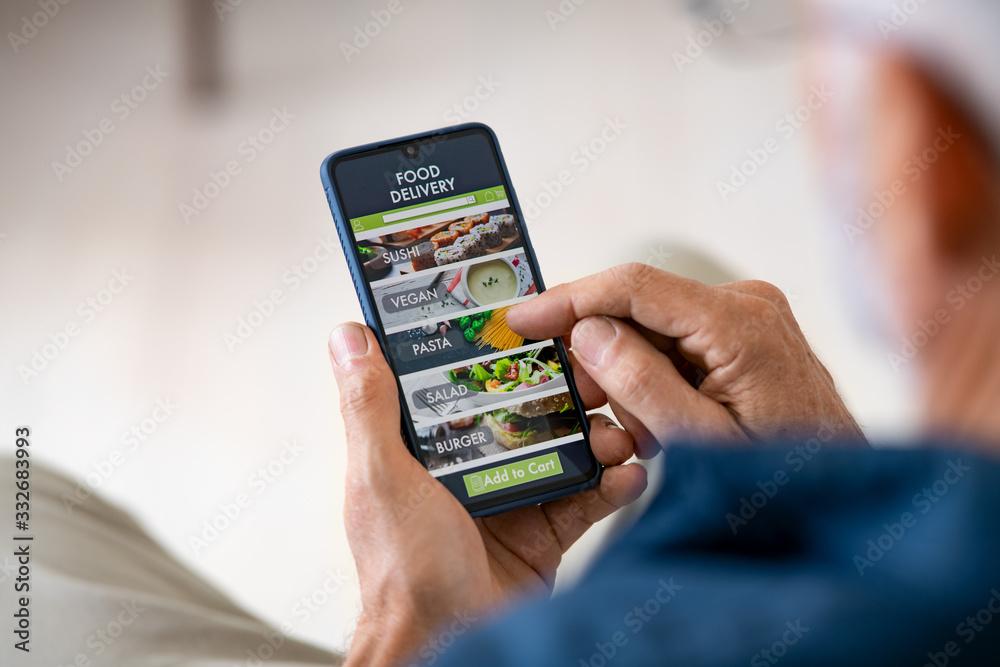 Fototapeta Man using mobile app to order delivery food