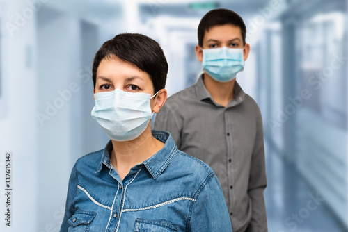Fototapety, obrazy: Two people wearing protective surgical mask in hospital or medical center. Caucasian middle-aged woman and teenage boy in medical masks. COVID-19 outbreak prevention. Coronavirus pandemic concept.