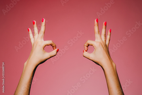 Woman's hands with bright manicure isolated on pink background okay super gestur Canvas Print