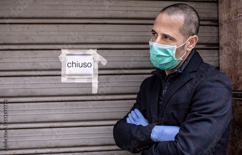 Fotomural Un uomo rasato  con mascherina giacca e guanti è sconschiude la  serranda  della sua attività a causa delle restrizioni per la pandemia