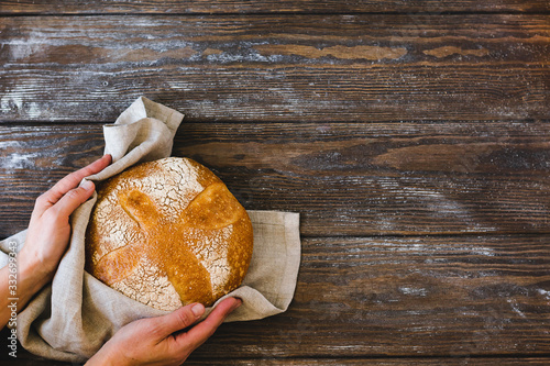 Plakat Rustykalny  a-woman-holds-in-her-hands-a-loaf-of-fresh-baked-homemade-bread-rustic-wooden-background-rustic