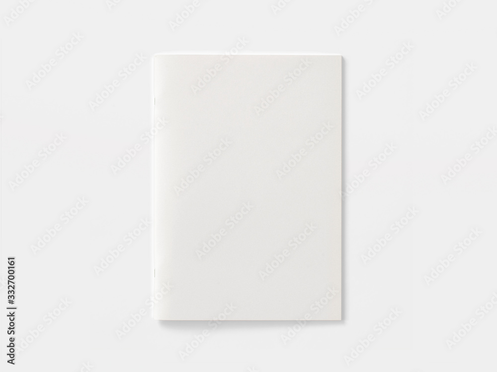 Fototapeta Blank portrait magazine or brochure isolated on white. Front cover top view as mockup template for your design presentation