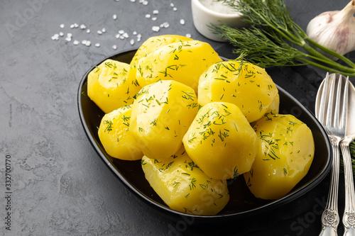 Carta da parati Delicious boiled potatoes with dill in a black plate.