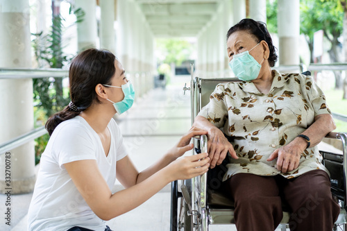 Young Asian grandchild taking care her grandmother sitting on wheelchair Fototapeta