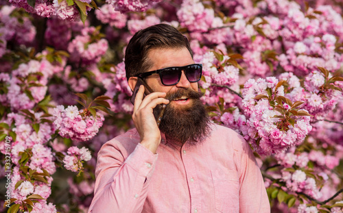 Bearded man in pink shirt talking by phone Canvas Print