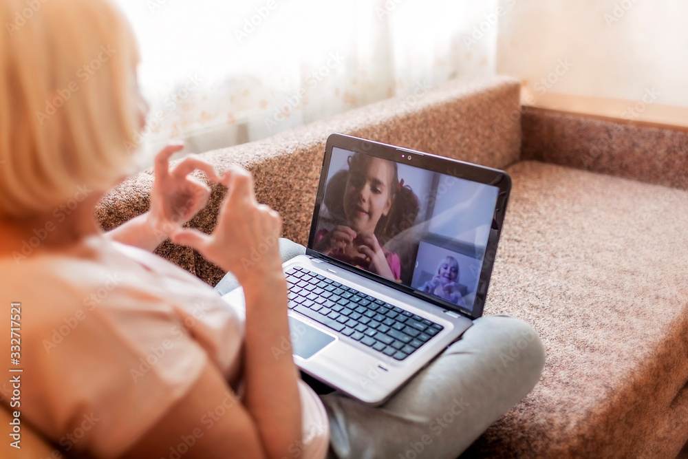 Fototapeta Cute girl talking with her grandmother within video chat on laptop, life in quarantine time