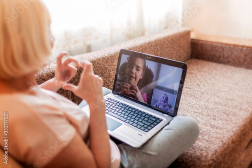 Obraz Cute girl talking with her grandmother within video chat on laptop, life in quarantine time - fototapety do salonu