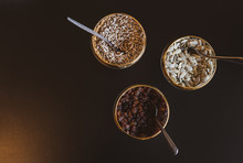 Three Bowls With  Raisins Pumpkin And Sunflower Seeds With Spoons Inside On The Brown Background. Blank Space Image.