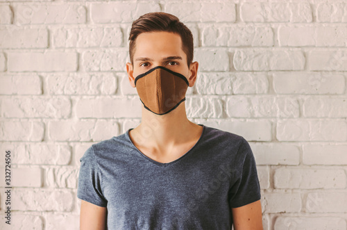 Fototapeta Young man in protective face mask as preventive measure from chinese coronavirus COVID-19. Hipster man wearing professional face mask for protection against pollution or nCov-19. Personal protection obraz