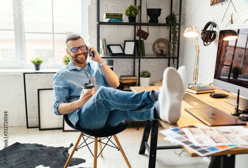 Obraz Young man is talking on the phone   at workplace. - fototapety do salonu