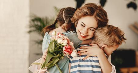 Little children congratulating and hug mother in kitchen.