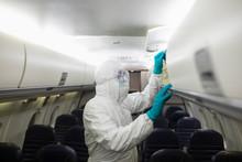 Worker In Clean Suit Sanitizin...
