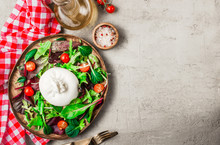 Salad With Italian Burrata Cheese, Arugula, Spinach, Cherry Tomatoes And Olive Oil Served On Wooden Plate. Top View. Light Gray Concrete Background