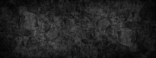 Black grunge background. Texture of cracked stone surface. Black rock grunge background with copy space for your design.