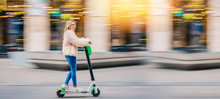 Young Woman Girl Riding Electric Scooter Downtown In City Street Urban
