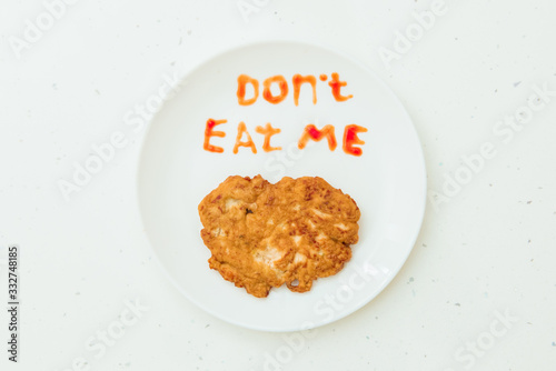 Valokuvatapetti White plate with fried meat, warning text. Veganism concept