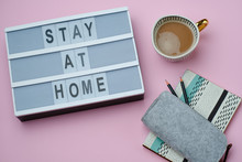 Top View Of Flat Lay Composition With Message Stay Home With Coffee And Book On Pink Background