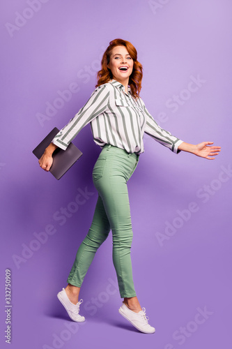Full length profile side photo of charming cute ginger hair woman executive manager hold laptop walk go to start-up everyday meeting wear good look clothes isolated violet color background - 332750909