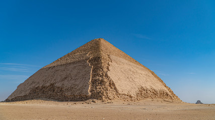 The Bent Pyramid is an ancient Egyptian pyramid located at the royal necropolis of Dahshur, approximately 40 kilometres south of Cairo, built under the Old Kingdom Pharaoh Sneferu. Egypt