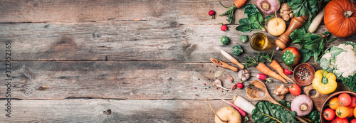 Fototapeta Fresh ingredients for healthy cooking or salad making on wooden background. Top view. Copy space. Diet or vegetarian food concept. Assortment of churd, pumpkin, carrot, pepper, cabbage, garlic obraz