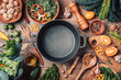 canvas print picture - Various organic vegetables ingredients and empty iron cooking pot, wooden bowls, spoons on wooden background. Top view, copy space. Organic vegetables ingredients for vegan cooking. Clean eating food