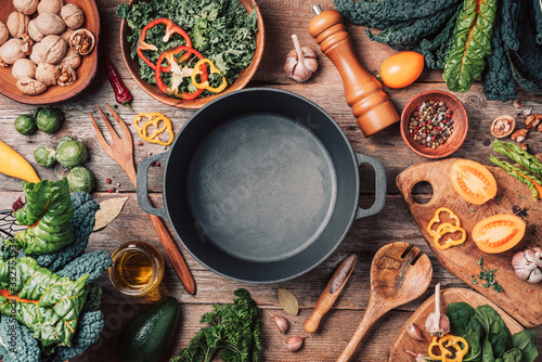 Fototapeta Various organic vegetables ingredients and empty iron cooking pot, wooden bowls, spoons on wooden background