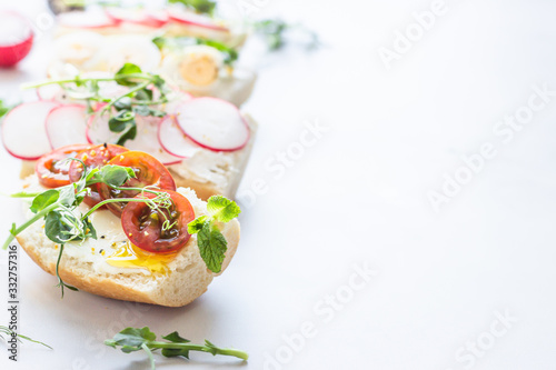 Photo Variety of sandwiches with quail eggs, tomatoes, radish and micro green on a light grey background, selective focus