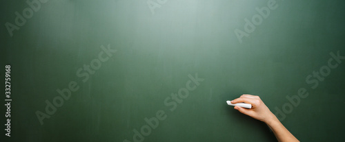 Hand of a teacher drawing white line with chalk on a green chalkboard, with copyspace for your individual text.