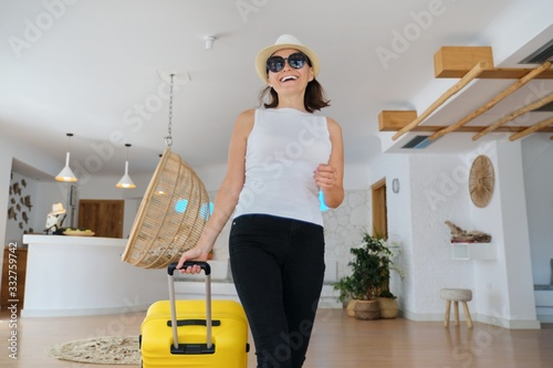 Fotografie, Tablou Woman guest tourist with suitcase in hotel lobby interior