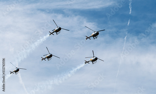 Fotografie, Tablou Formation of five military helicopters flies over the ground