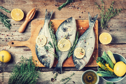 Fototapeta Raw dorado fish with ingredients, lemon, herbs, oil, vegetables and spices on wooden cutting board over wood background. Top view. Healthy food diet. Food pattern. Seafood concept. obraz