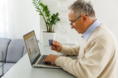 Senior man at laptop paying with credit card for online shopping Fototapet